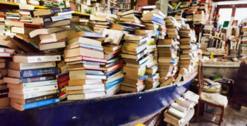 Piles of used books within a blue boat in a bookshop
