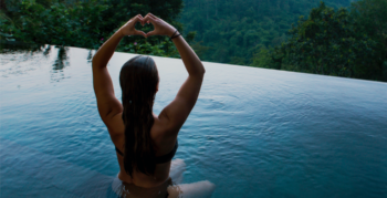 A woman performs yoga while sitting in an infinity pool looking over rainforest landscape