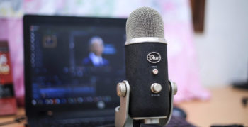 Podcast microphone in front of laptop display of video editing software