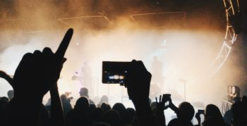 Crowd take photos of a band on their smartphones at a gig