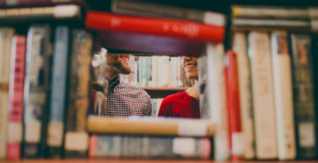 Two people meeting and laughing in a library