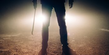 A man with a crowbar looms menacingly in front of car headlights